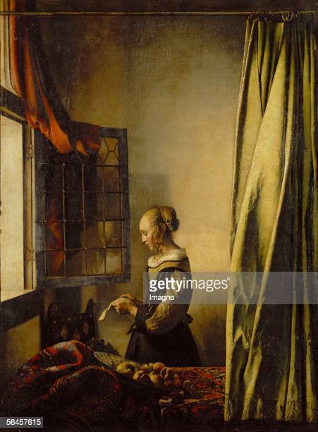 a girl reading a letter by an open window ストックフォトと画像