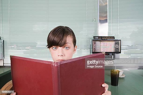 girl reading a menu in a diner - speisekarte stock-fotos und bilder