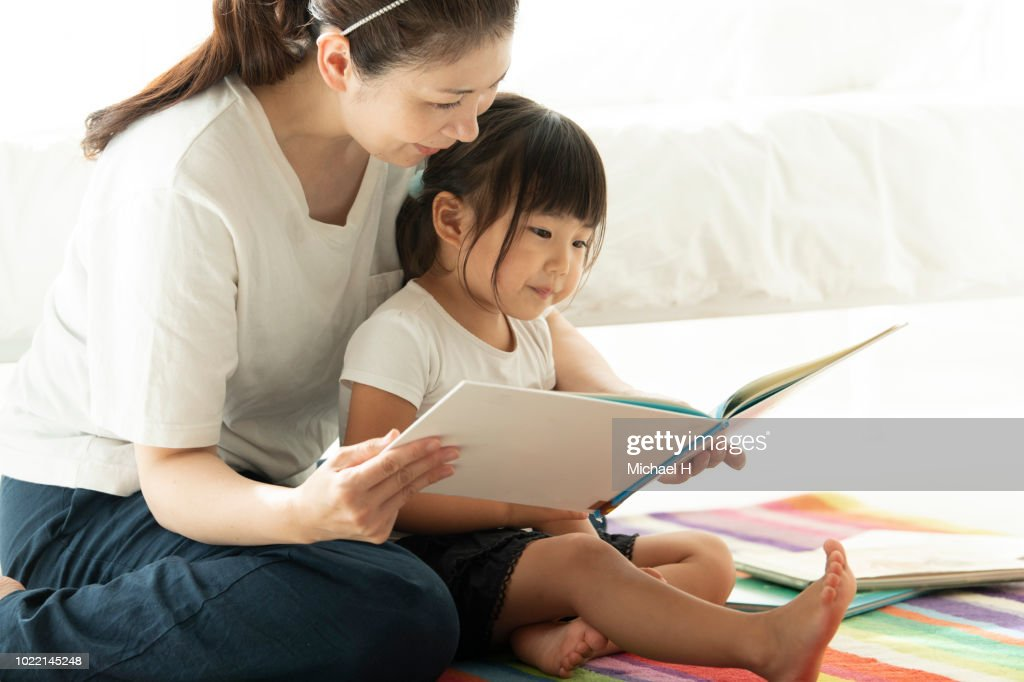 A girl reading a picture book with her mother : ストックフォト
