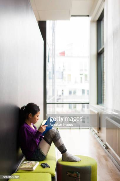 Girl (8-9) reading book at school