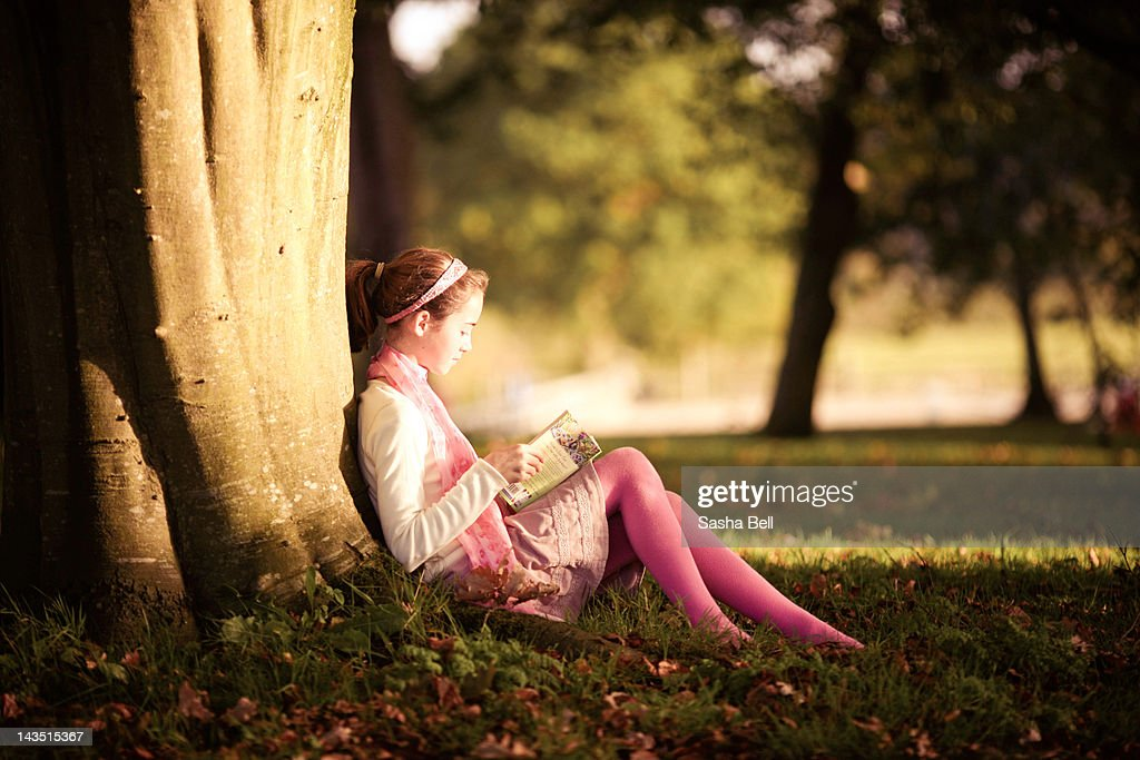 Girl reading book in autumn : Stock Photo