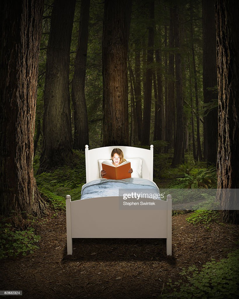 Girl reading book in bed located in a forest : Stock Photo