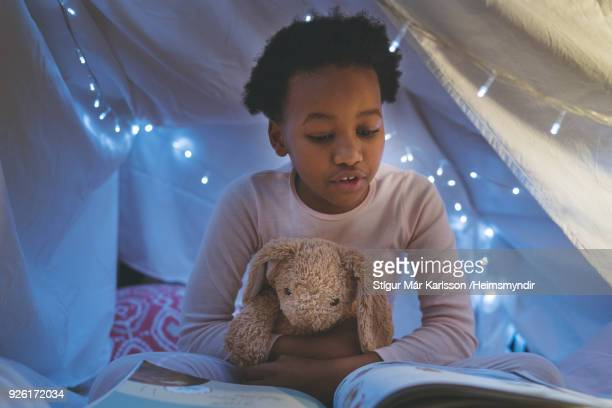girl reading book in illuminated tent - picture book stock pictures, royalty-free photos & images