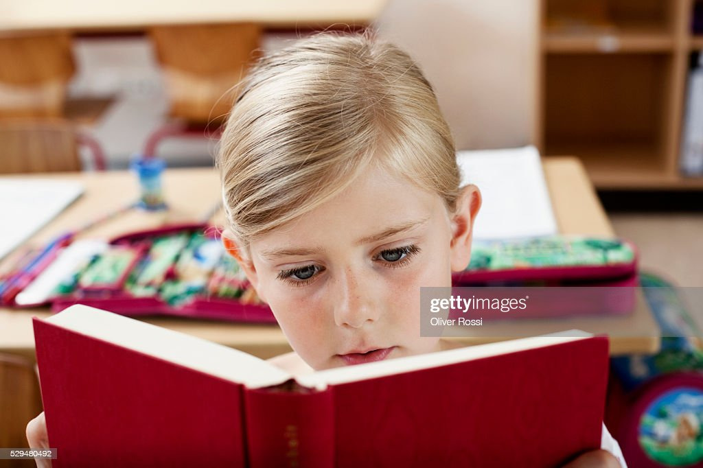 Girl reading book in school : Stock Photo