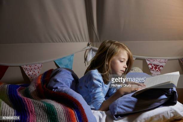 girl reading book in tent at night - richard drury stock pictures, royalty-free photos & images