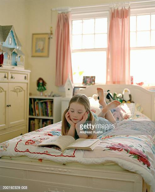 Girl (8-10) reading book on bed in bedroom