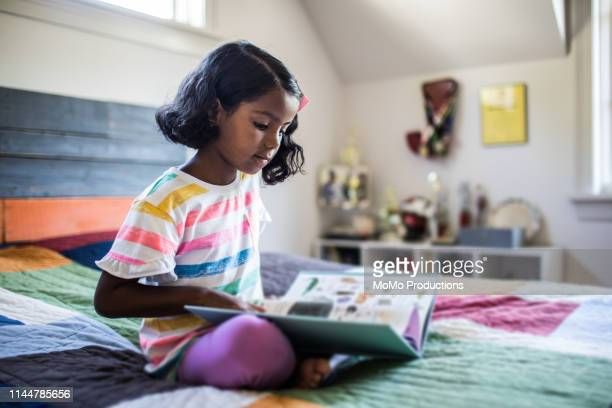 girl reading book on her bed - reading stock pictures, royalty-free photos & images