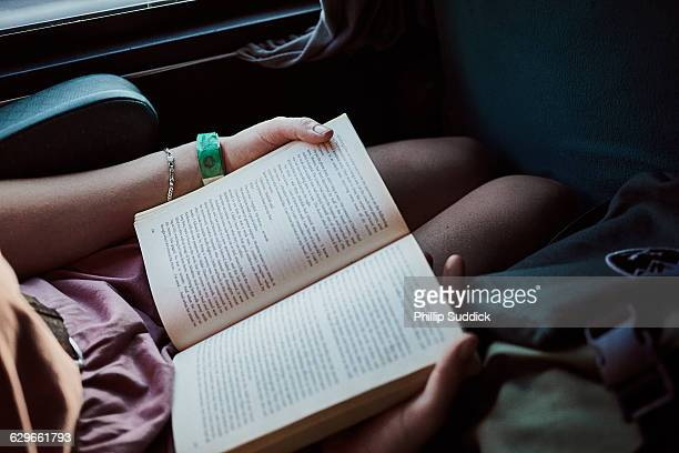 girl reading book on old train travelling