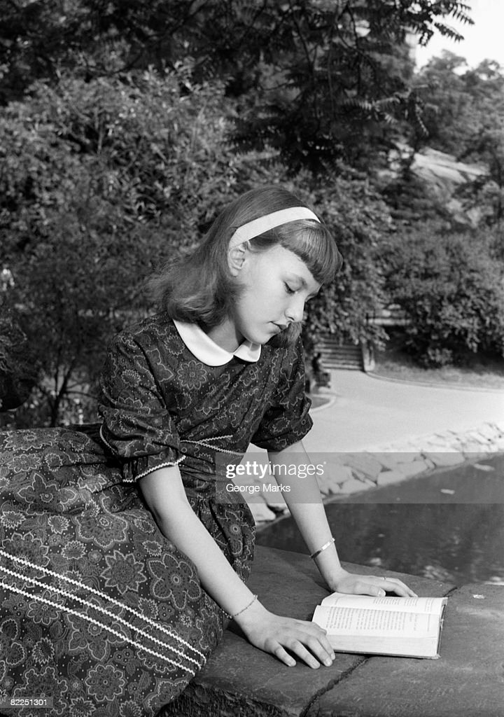 Girl (12-13) reading book, sitting on bridge in park : Stock Photo