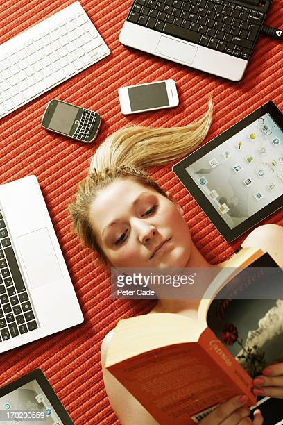 Girl reading book surrounded by technology