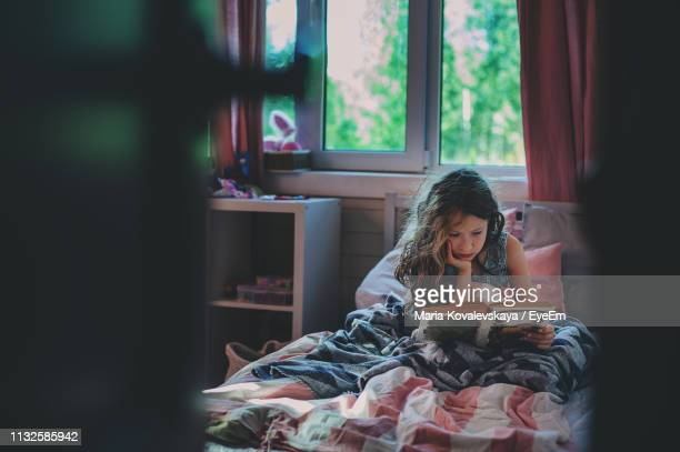 girl reading book while sitting on bed at home - solo una bambina femmina foto e immagini stock