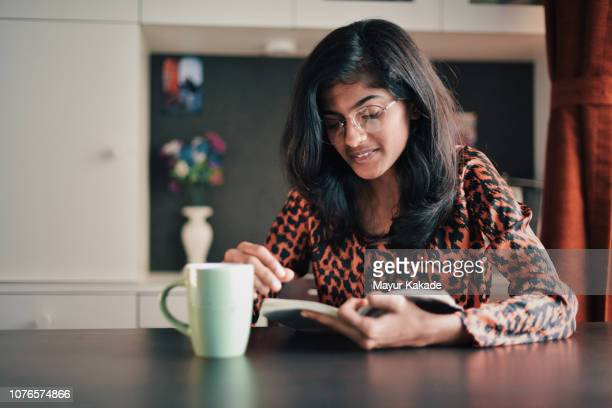 girl reading book with a coffe mug - south asia stock pictures, royalty-free photos & images