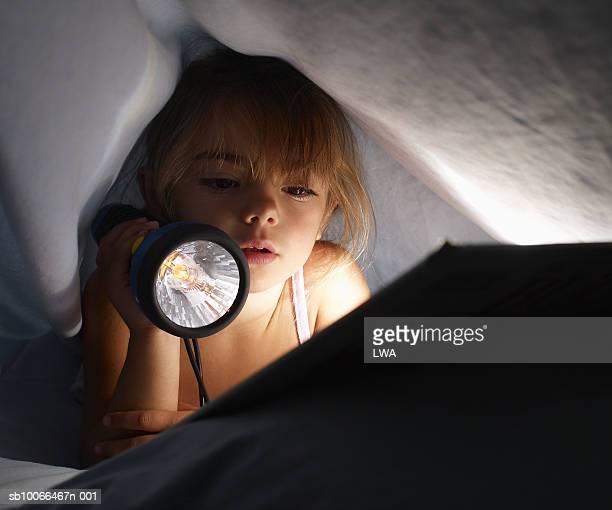 girl (5-6) reading book with torch under sheet, close-up - ein mädchen allein stock-fotos und bilder