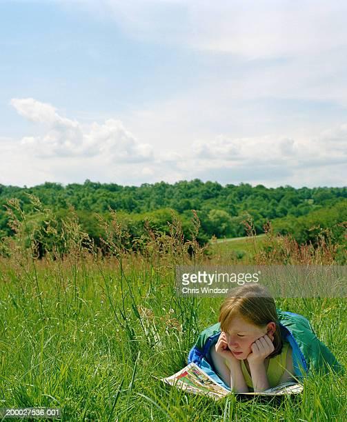 Girl (9-11) reading comic in field