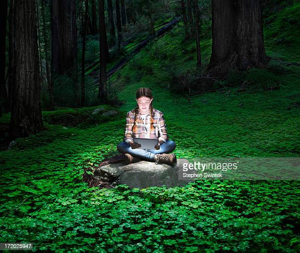 Girl reading glowing tablet in redwood forest