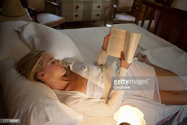 girl reading in bed - donne bionde scalze foto e immagini stock