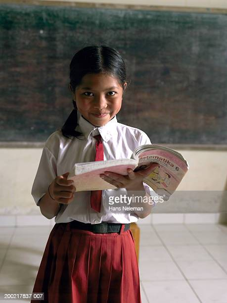 Girl (8-10) reading in front of class, portrait, close-up