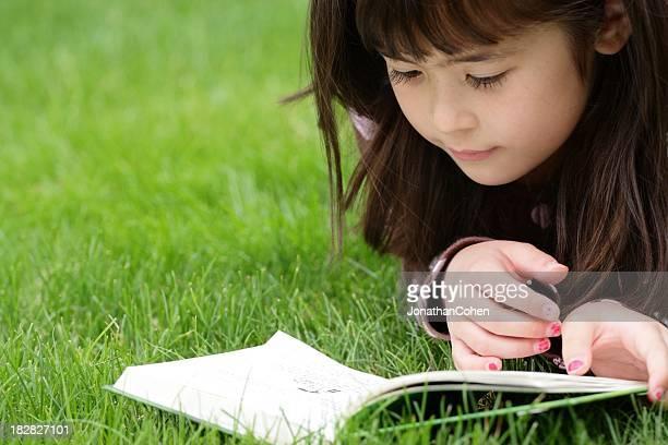 Mädchen lesen im Gras