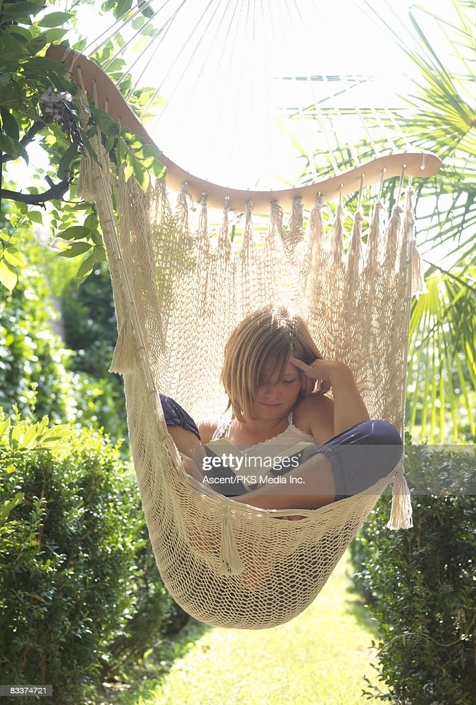 Good Girl Reading In Hanging Hammock Chair In Garden Stock Photo | Getty Images