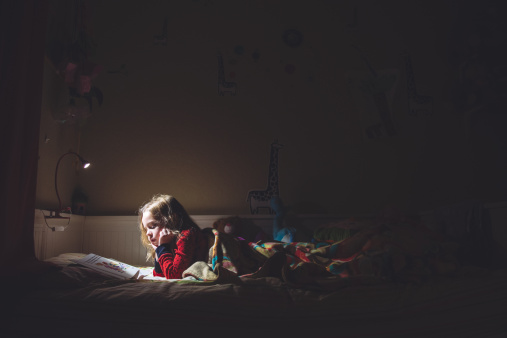 Girl reading in her bed at night - gettyimageskorea