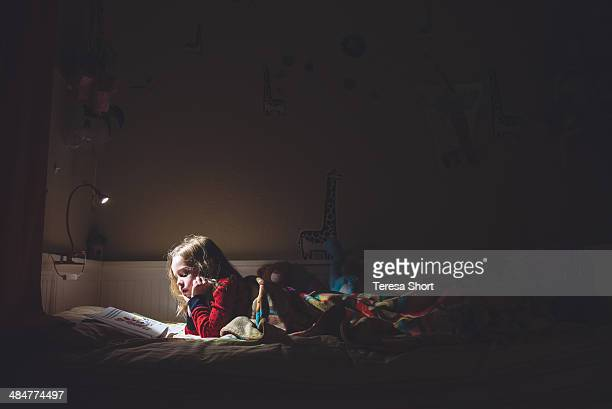 girl reading in her bed at night - lamp stock-fotos und bilder