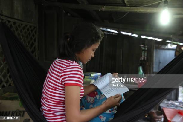 Girl reading in her slum home Battambang Cambodia