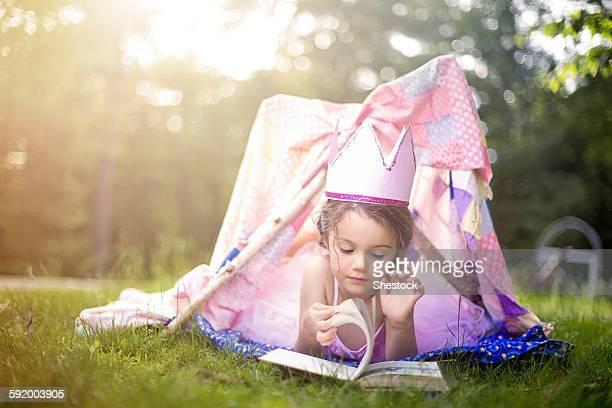 Girl reading in tent in backyard