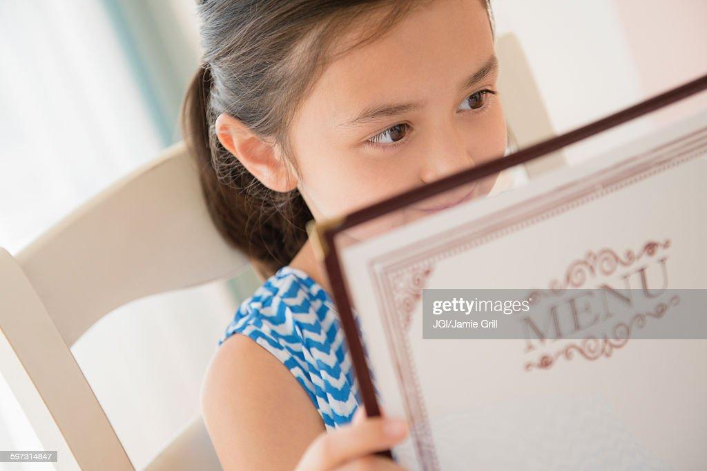Girl reading menu in restaurant : Stock Photo