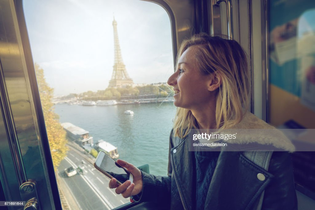 Young woman in the subway in Paris text messaging on mobile phone.