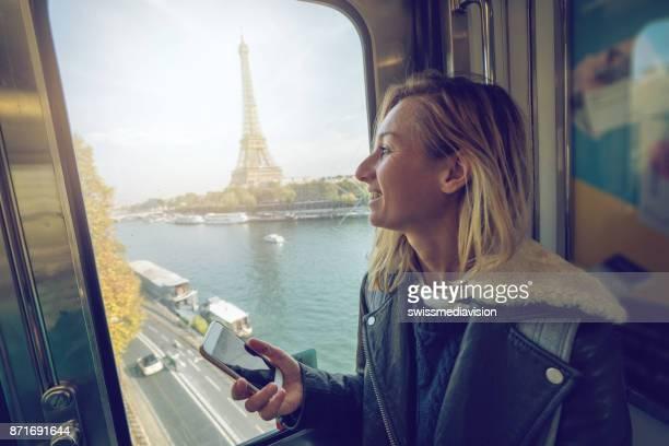 Jeune fille lisant message sur téléphone tandis que le métro parisien
