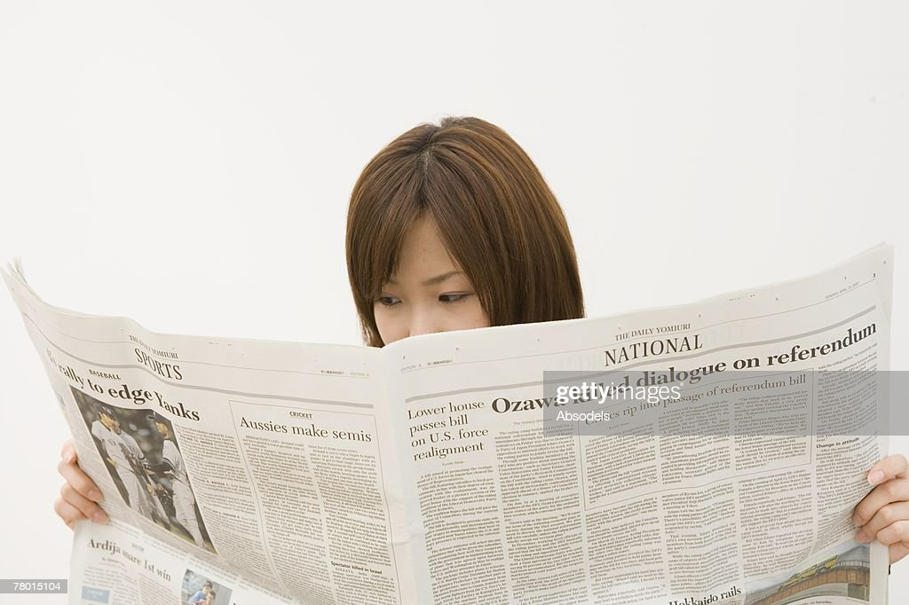 A girl reading newspaper : Stock Photo