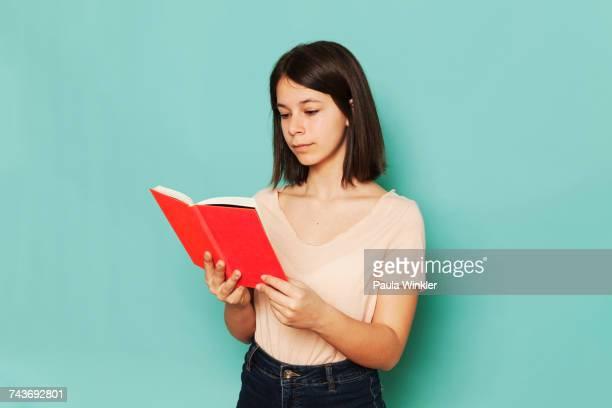 girl reading novel against turquoise background - 12歳から13歳 ストックフォトと画像