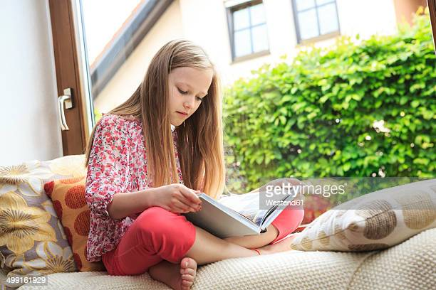 girl reading on a couch - little girls bent over stock photos and pictures