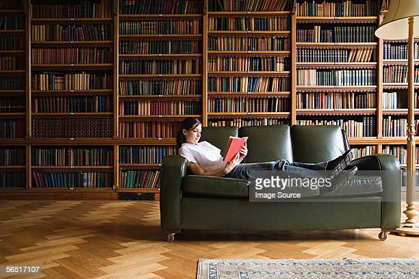 girl reading on a sofa in the library - library stock pictures, royalty-free photos & images