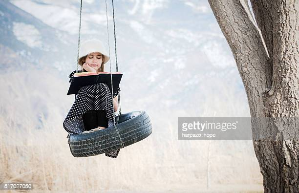 Girl reading on a tire swing.
