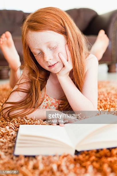 girl reading on living room floor - redhead girl stock photos and pictures