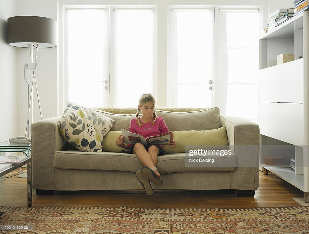 Reading On Sofa In Living Room Bildbanksbilder Getty