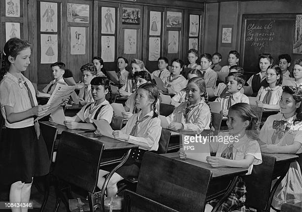 A girl reading to her sixth grade class circa 1950's