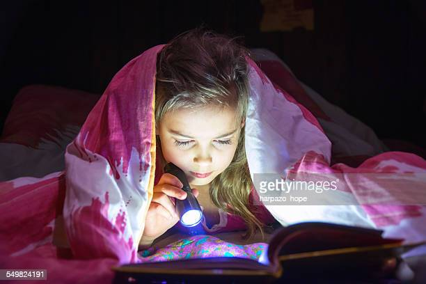 Girl reading with a flashlight.