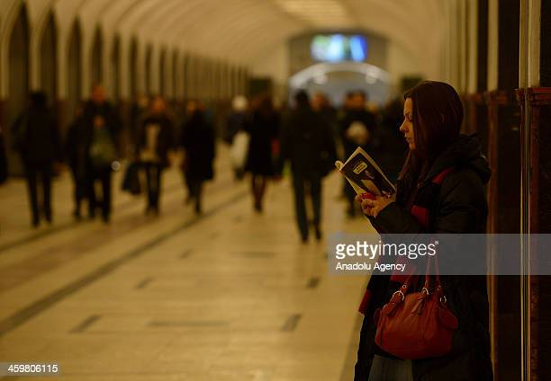 A girl reads a book at Mayakovskaya metro station in Moscow Russia on December 28 2013 One of the largest underground metro system in the world the...