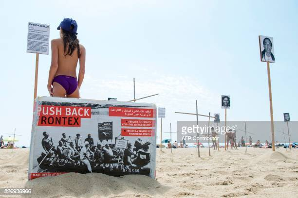 A girl reads a placard telling the story of dead migrant Idrissa Diallo next to crosses and photographs of other dead migrants and refugees on...