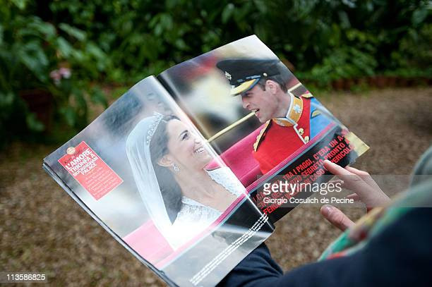 A girl reads an Italian magazine showing photographs of Prince William Duke of Cambridge and Catherine Duchess of Cambridge following their wedding...