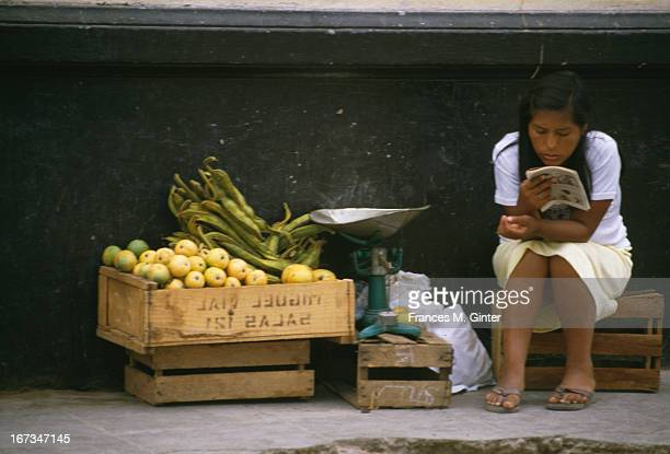 A girl reads her book next to a small lemon stand Nazca Peru March 1984