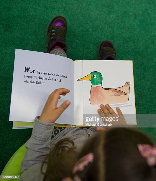 A girl reads in a children's book during the presentation of Project 'Lesestart' in a Libary for Children on November 15 2013 in Berlin Germany The...