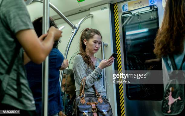A girl reads on mobile phone in a subway train In the first half of 2017 the Chinese users of mobile music video games and reading grew by above 4%