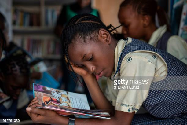 A girl reads through a book in the IRead mobile library on January 30 2018 The IRead initiative is the first mobile library service in Nigeria The...