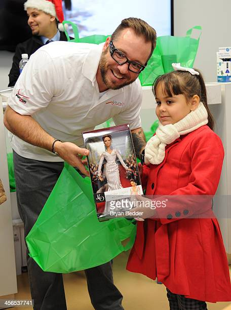 A girl receives her holiday gifts and a Barbie doll depicting Jennifer Lopez at the event organized by Viva Movil for Jennifer Lopez who rings in the...