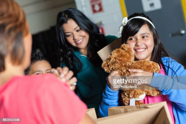Girl receives teddy bear during charity event