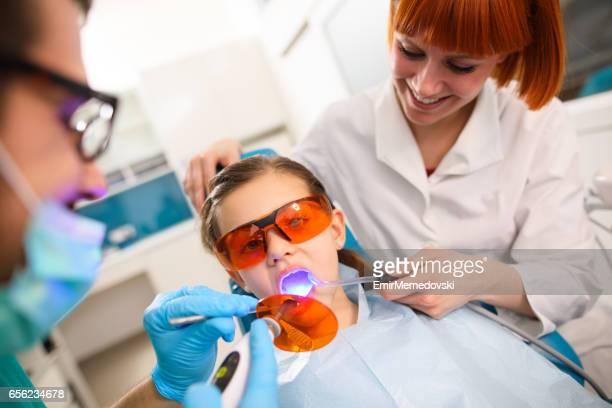 Girl receiving dental filling drying procedure.