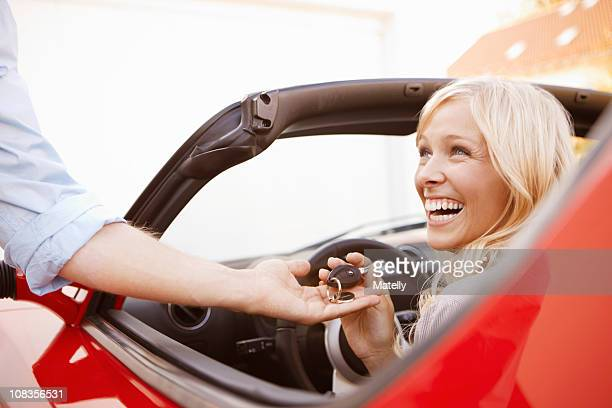 Girl receiving keys to an electric car